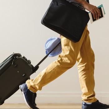 traveler walking with rolling luggage
