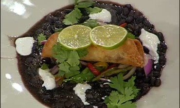 Tacos Dorados over Black Beans with Tequila Crema