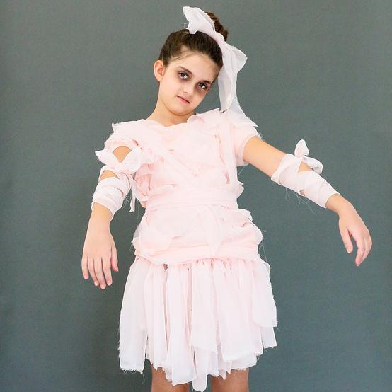 girl posing in light pink mummy costume