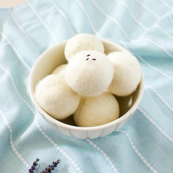 wool dryer balls in bowl over blue blanket