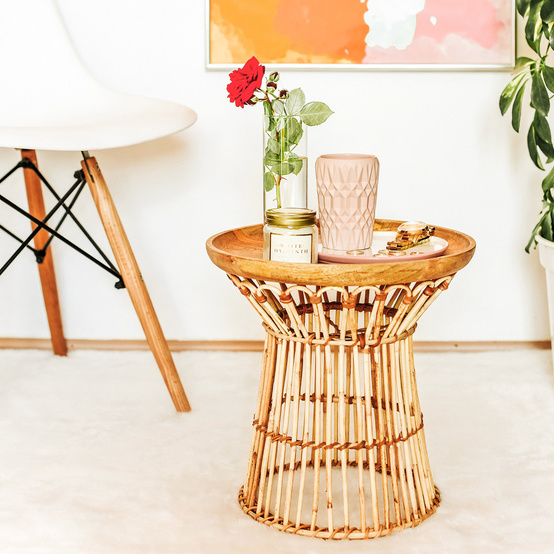 completed rattan side table by white chair