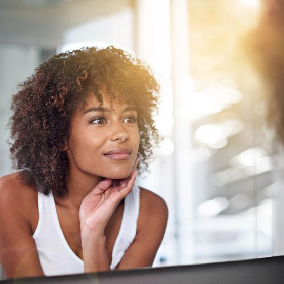 woman in mirror with glowing skin