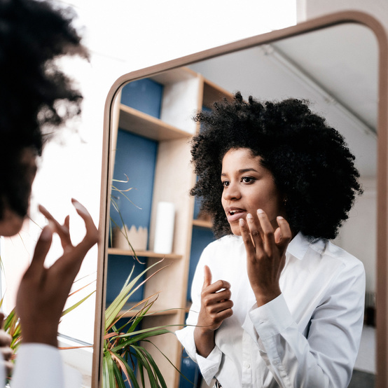 woman putting glycolic acid on face in mirror