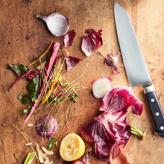 scraps of produce on cutting board with knife