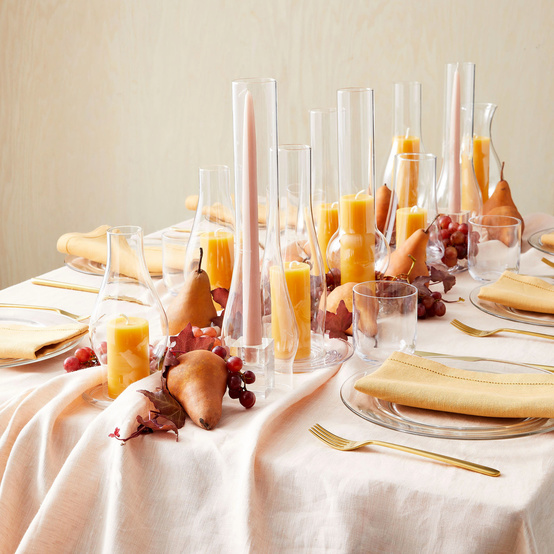 table decorated with candles in glass lamp chimneys and fruit