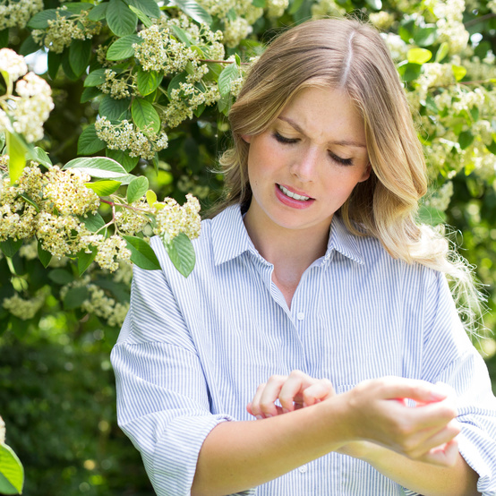 Woman Itching Her Skin in the Garden