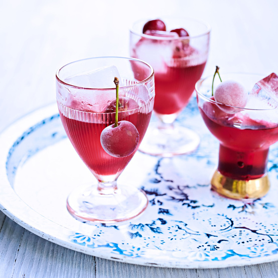 cherry bounce cocktail garnished with frozen cherries