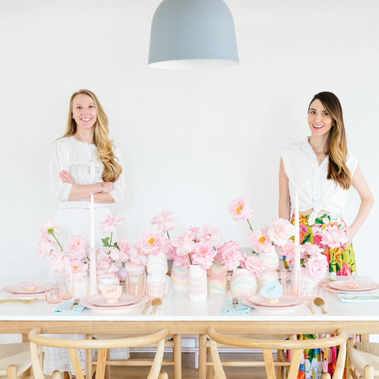 two women with pink flower decorated table