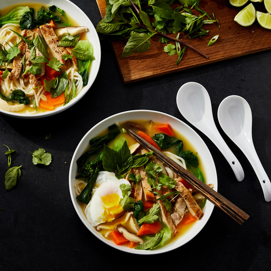 shanghai noodle soup served with mint and lime wedges