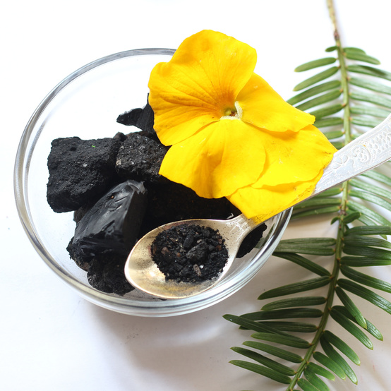 bowl of charcoal with yellow flower and spoon