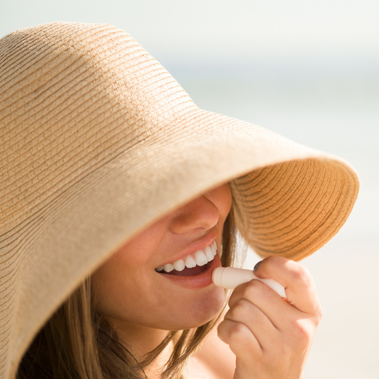 woman in sunhat applying chapstick
