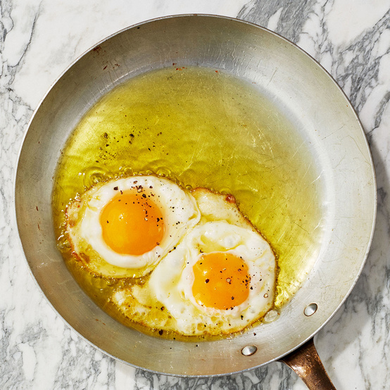 olive-oil fried eggs in pan
