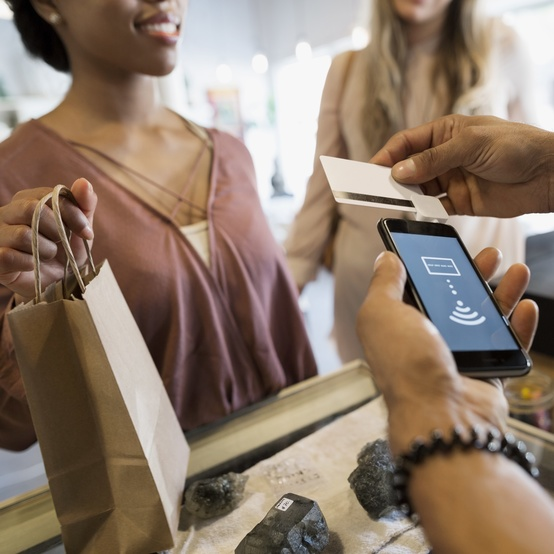 A woman is paying for an item with her credit card in a store
