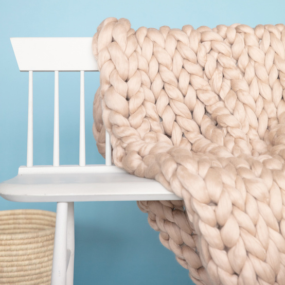 completed arm knit blanket folded over white bench