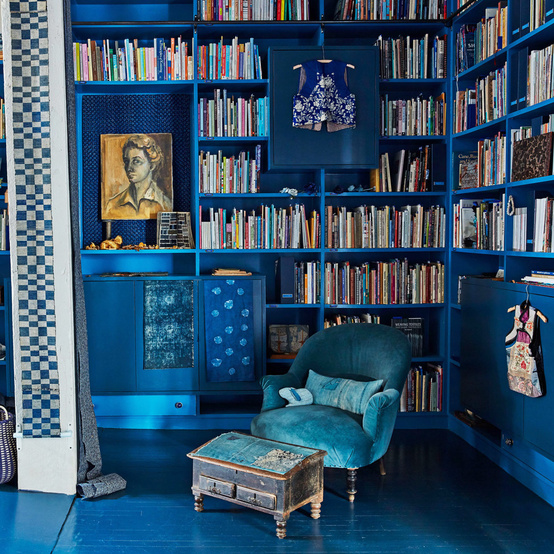 blue library with textiles hanging and handmade baskets