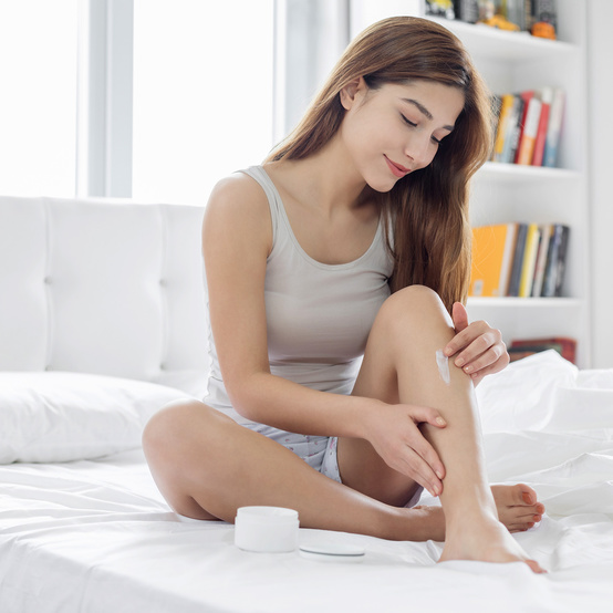woman rubbing lotion on legs