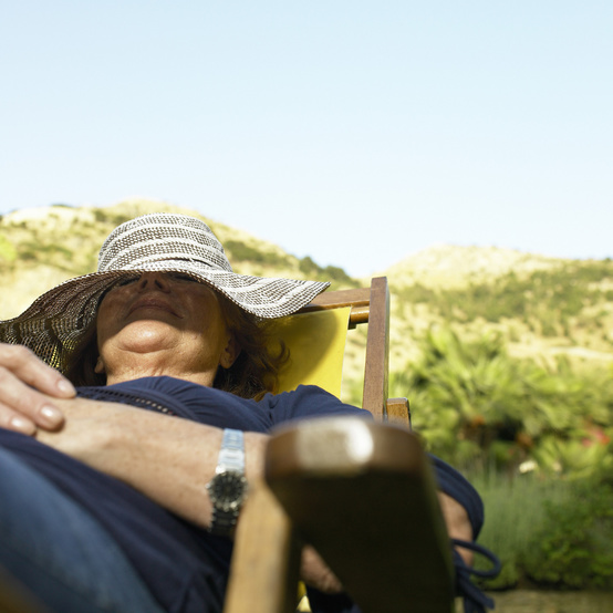 mature woman relaxing in deckchair in garden, hat covering face