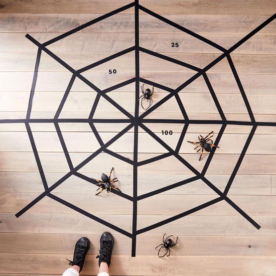 black tape web on floor with plastic spiders