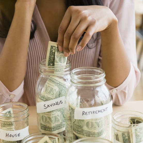 woman saving money in jars