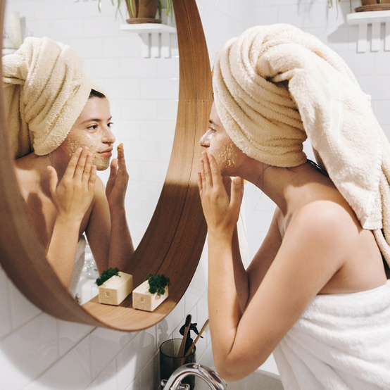 woman applying face mask looking in mirror