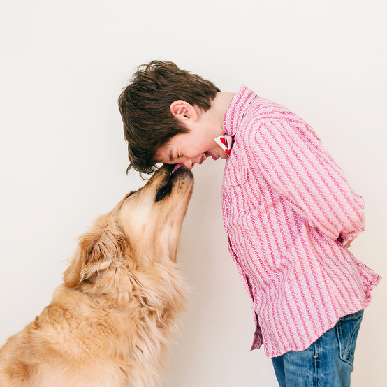 dog licking boys face against white wall