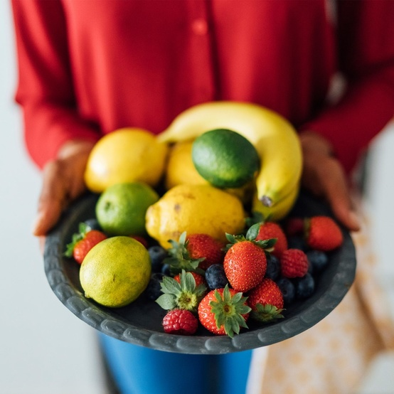 woman holding a bowl of fruit