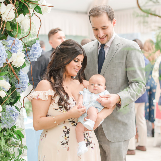 charitable baptism celebration couple with baby by floral arch