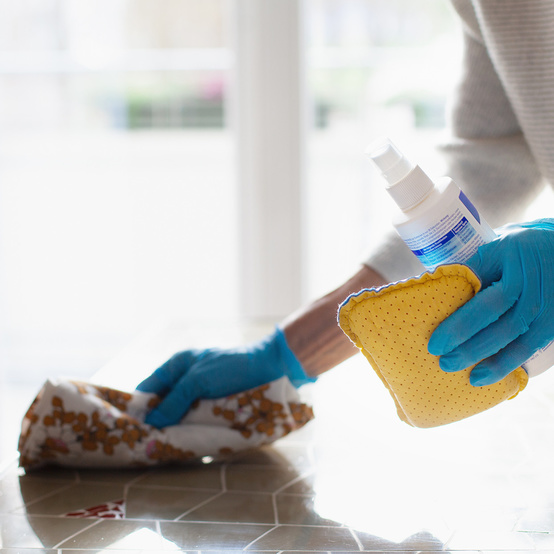 woman wearing blue gloves cleaning countertop with product and cloth