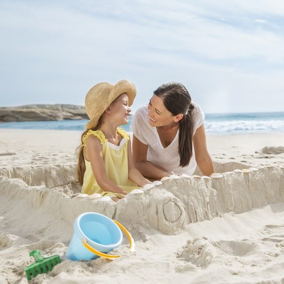 Mom and Daughter Building a Sandcastle on the Beach