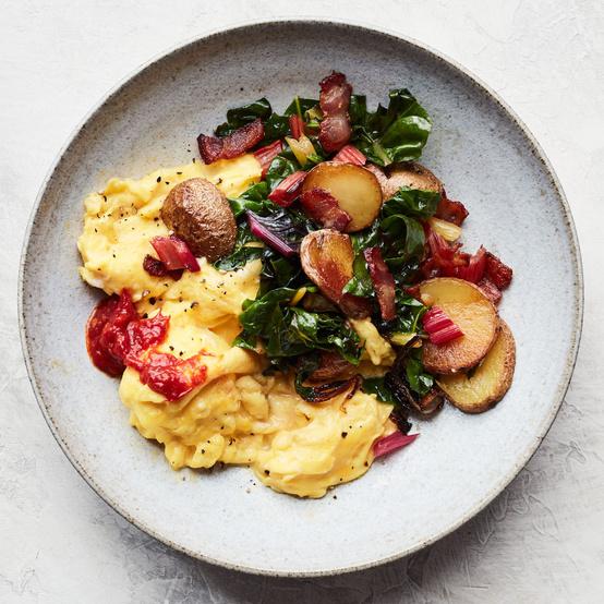 bacon potato and swiss chard scramble served on grey plate
