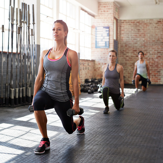 crossfitters doing lunges while holding free weights