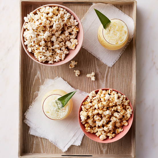 movie-theater-style popcorn served on tray with cocktails