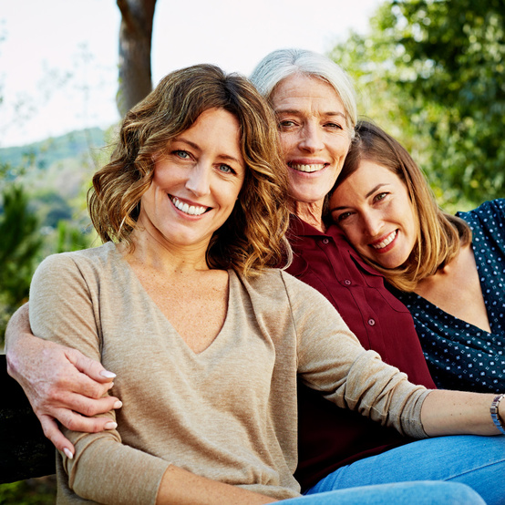 Portrait of happy mother sitting with daughters on park bench