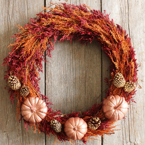This fall wreath is made with dried caspia, metallic-painted pumpkins, and gilded pinecones.