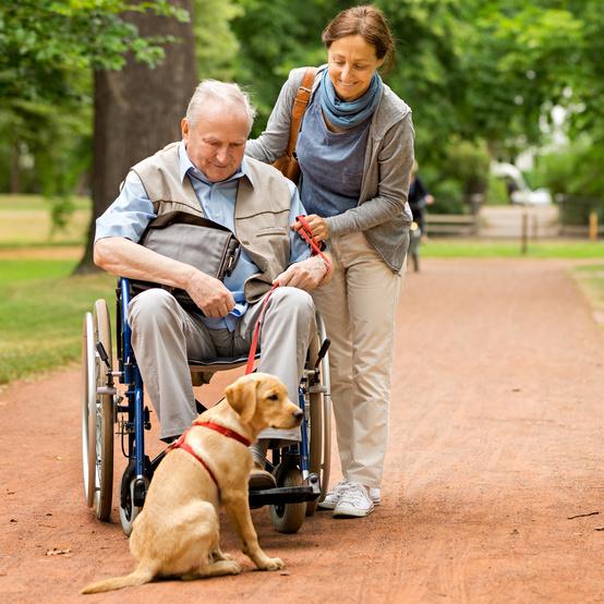 senior man with dog and caregiver