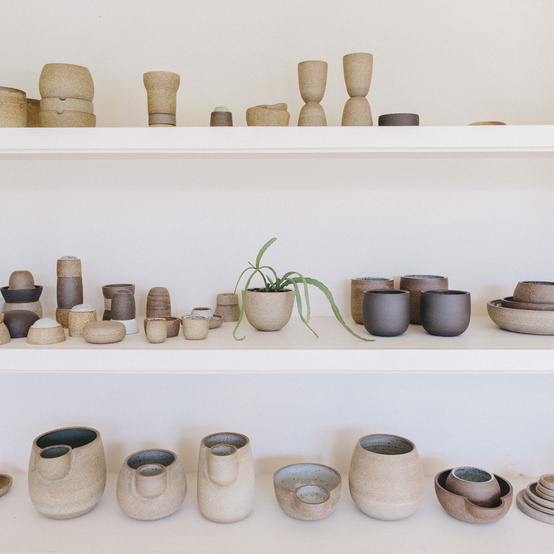 shelves of ceramic pottery by julie cloutier