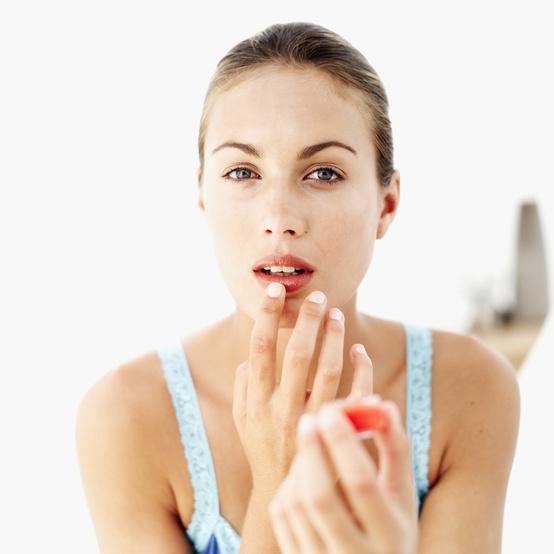 young woman applying lip gloss