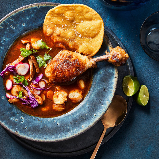 red chicken pozole served with sliced radishes