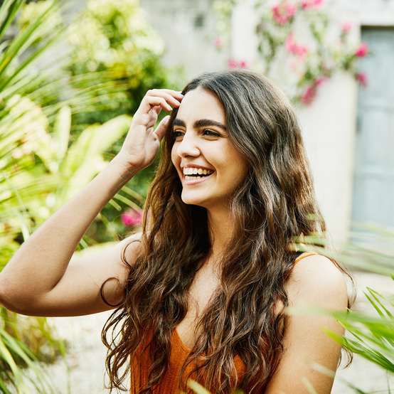 woman laughing in front of greenery