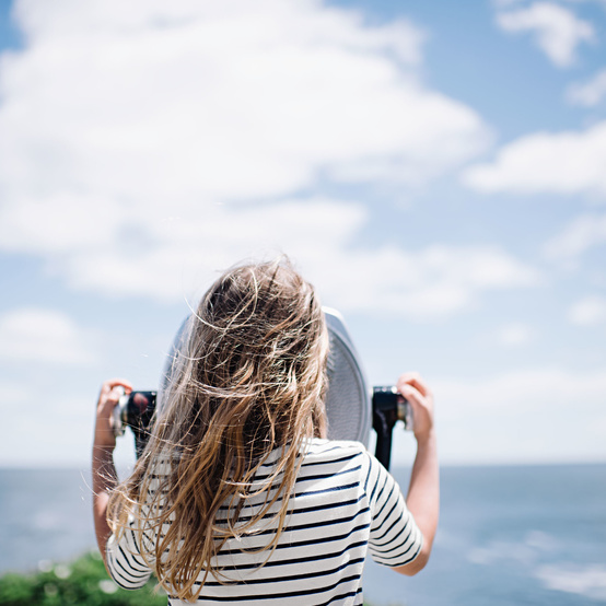 girl looking through a viewfinder on the beach
