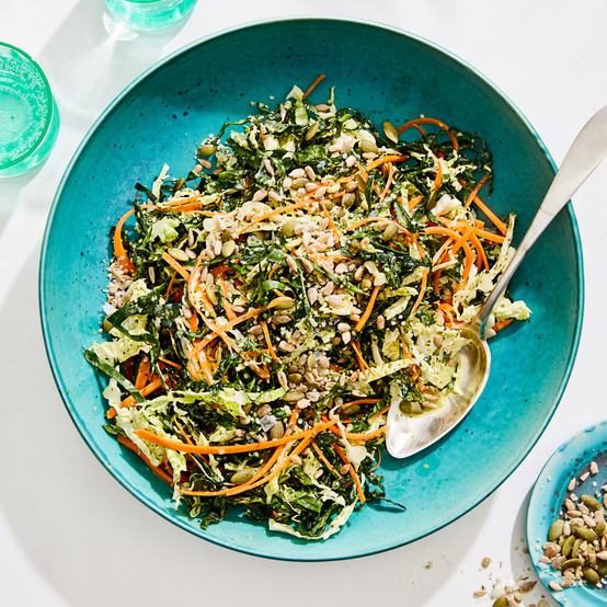 cilantro-lime kale slaw with seeds served in a blue bowl