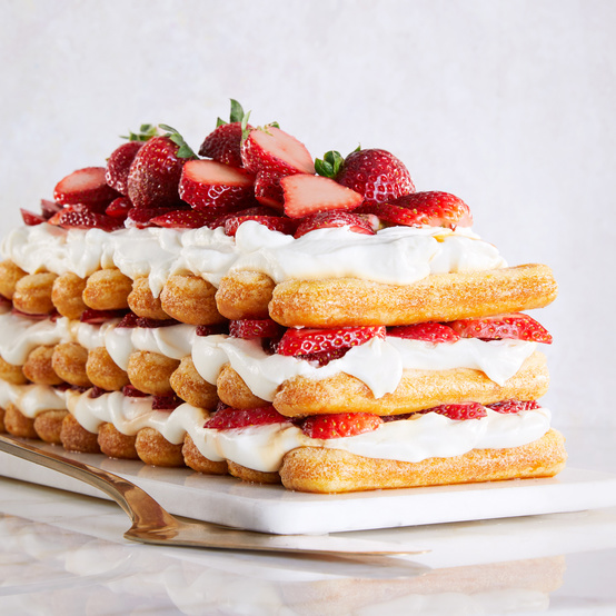 strawberries-and-cream stack cake topped with fresh strawberries