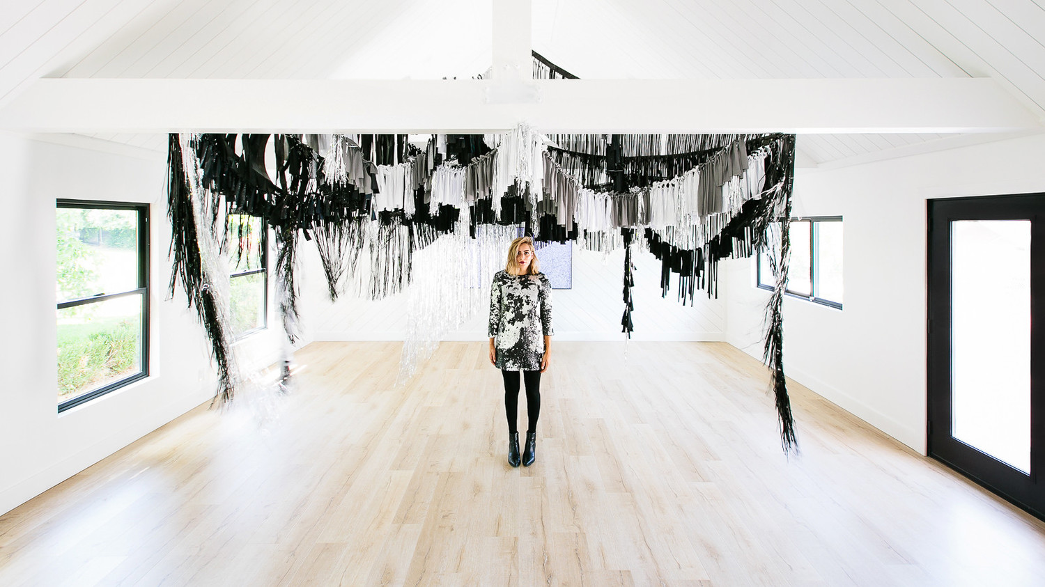 haunted movie house black white silver fringe streamers and woman standing in front