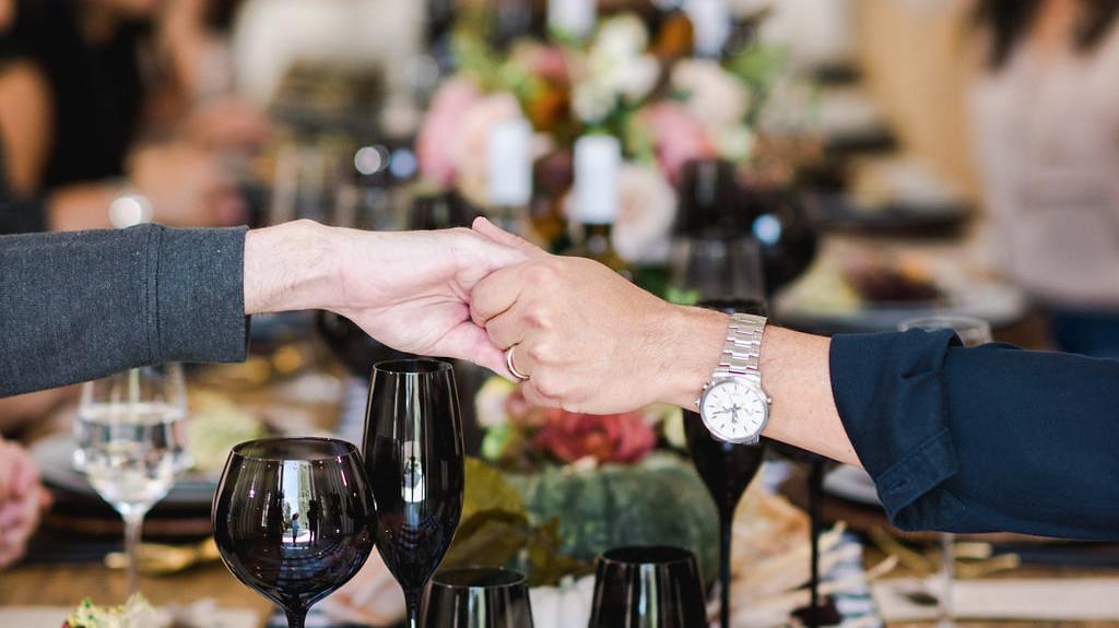 朋友们在朋友吃饭前握着手