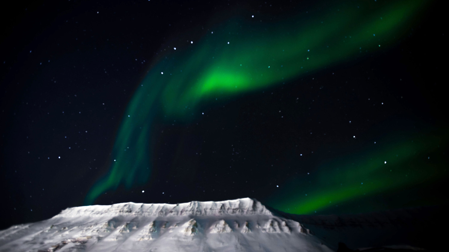 green northern lights above snow-capped mountain