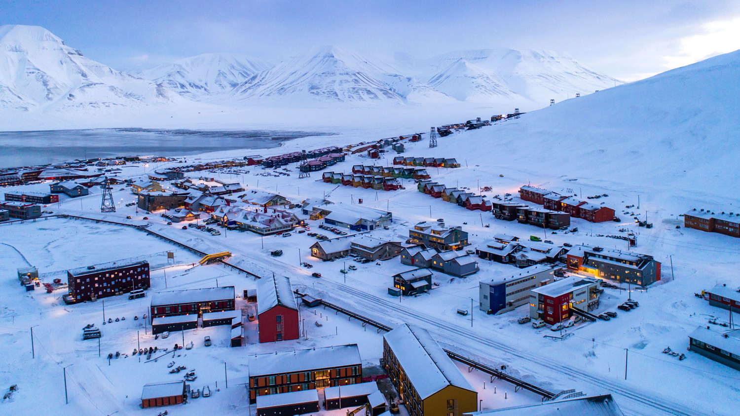 the town of svalbard below snow-capped mountains