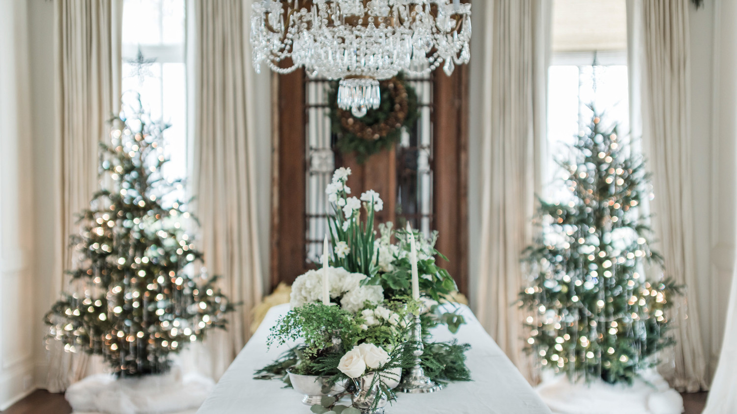 holiday dining table with chandelier and trees