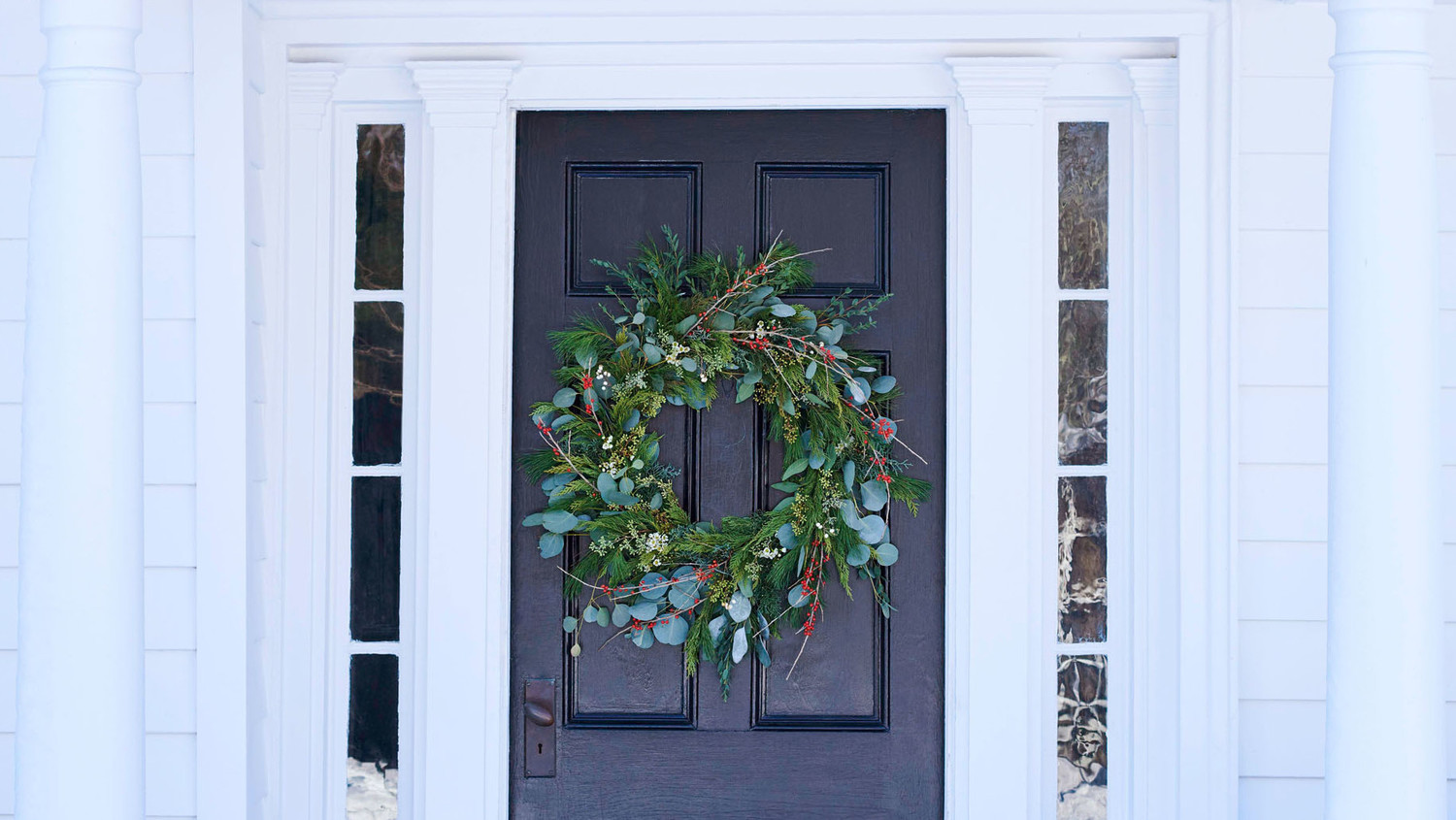 winter wreath on front door of white house