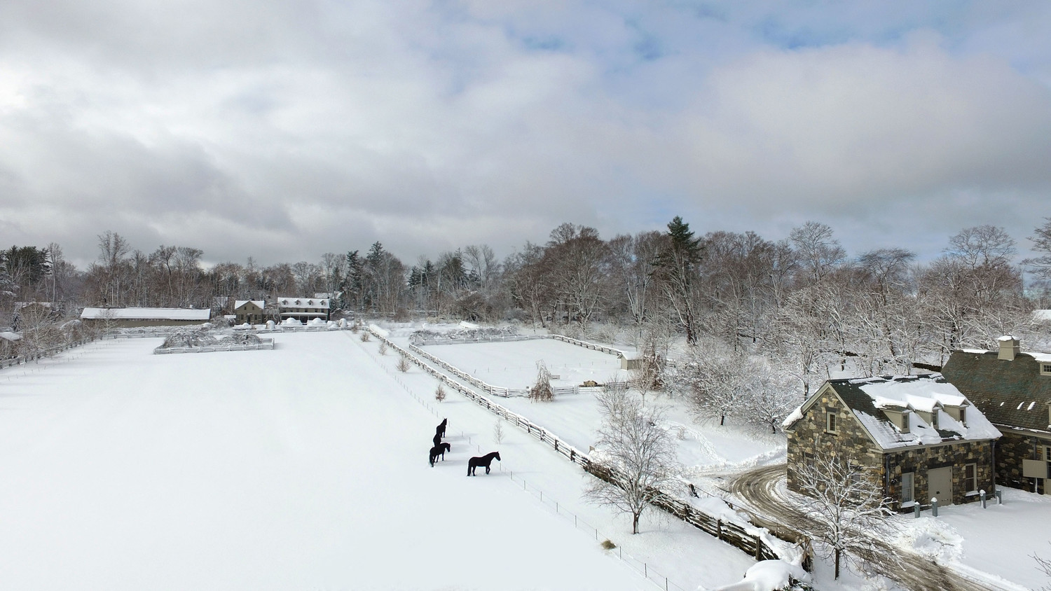 drone shot of marthas home in winter with horses