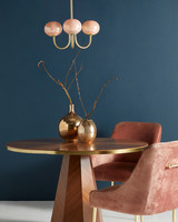 gold and wood dining table in dark blue room
